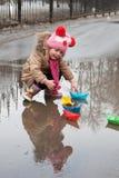 Παιχνίδια μικρών κοριτσιών με τα σκάφη εγγράφου Στοκ Φωτογραφίες