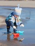 Παιχνίδια μικρών παιδιών με τα σκάφη εγγράφου Στοκ φωτογραφία με δικαίωμα ελεύθερης χρήσης