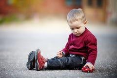 Παιχνίδια μικρών παιδιών με το αυτοκίνητο παιχνιδιών Στοκ φωτογραφία με δικαίωμα ελεύθερης χρήσης