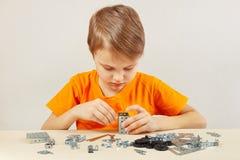 Παιχνίδια μικρών παιδιών με το μηχανικό κατασκευαστή στον πίνακα Στοκ φωτογραφία με δικαίωμα ελεύθερης χρήσης