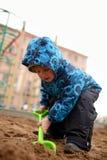 Παιχνίδια μικρών παιδιών σε ένα Sandbox με το φτυάρι των παιδιών στην παιδική χαρά στοκ φωτογραφία