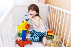 Παιχνίδια παιχνιδιών μικρών παιδιών στο άσπρο κρεβάτι Στοκ Εικόνες