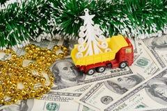 Παιχνίδια φορτηγών απορρίψεων και Χριστουγέννων στο υπόβαθρο από τα δολάρια Στοκ Εικόνα