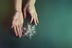 Παιχνίδια Χριστουγέννων στα όμορφα χέρια στο πράσινο υπόβαθρο Στοκ Εικόνες