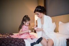 Παιχνίδια Mom με την κόρη της στο κρεβάτι και το αγκάλιασμα Στοκ εικόνες με δικαίωμα ελεύθερης χρήσης