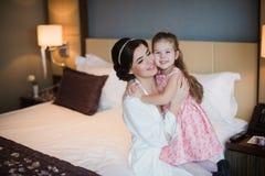 Παιχνίδια Mom με την κόρη της στο κρεβάτι και το αγκάλιασμα Στοκ Εικόνες