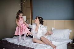 Παιχνίδια Mom με την κόρη της στο κρεβάτι και το αγκάλιασμα Στοκ φωτογραφία με δικαίωμα ελεύθερης χρήσης