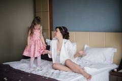 Παιχνίδια Mom με την κόρη της στο κρεβάτι και το αγκάλιασμα Στοκ Φωτογραφίες