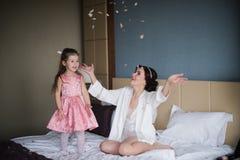 Παιχνίδια Mom με την κόρη της στο κρεβάτι και το αγκάλιασμα Στοκ εικόνα με δικαίωμα ελεύθερης χρήσης