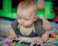 Παιχνίδι αγοράκι με το παιχνίδι πιάνων Στοκ Φωτογραφία