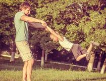 Παιχνίδι αγοριών ατόμων και γιων οικογενειακών πατέρων υπαίθριο Στοκ Φωτογραφίες