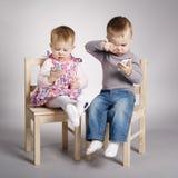 Παιχνίδι αγοριών και κοριτσιών με τα κινητά τηλέφωνα Στοκ Φωτογραφίες