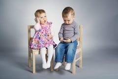 Παιχνίδι αγοριών και κοριτσιών με τα κινητά τηλέφωνα Στοκ Εικόνες