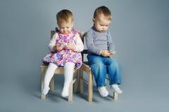 Παιχνίδι αγοριών και κοριτσιών με τα κινητά τηλέφωνα Στοκ Εικόνα