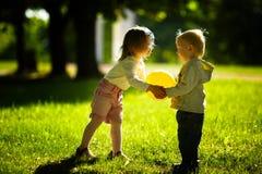 Παιχνίδι αγοριών και κοριτσιών με τη σφαίρα Στοκ Φωτογραφία