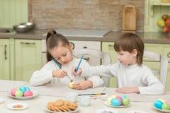 Παιχνίδι αγοριών και κοριτσιών παιδιών με τα αυγά Πάσχας και το γέλιο Στοκ Φωτογραφία