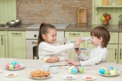Παιχνίδι αγοριών και κοριτσιών παιδιών με τα αυγά Πάσχας και το γέλιο Στοκ Εικόνες