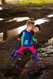 Παιχνίδι αγοριών και κοριτσιών στη λάσπη Στοκ Φωτογραφίες