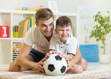 Παιχνίδι αγοριών και πατέρων παιδιών με το soccerball εσωτερικό Στοκ Εικόνα