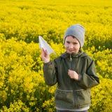 Παιχνίδι αγοριών με ένα αεροπλάνο εγγράφου στον τομέα με τα λουλούδια Στοκ εικόνες με δικαίωμα ελεύθερης χρήσης
