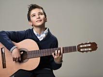 Παιχνίδι αγοριών με την ευχαρίστηση στην ακουστική κιθάρα στοκ φωτογραφία με δικαίωμα ελεύθερης χρήσης