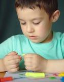 Παιχνίδι αγοριών με τη ζύμη παιχνιδιού χρώματος Στοκ εικόνα με δικαίωμα ελεύθερης χρήσης