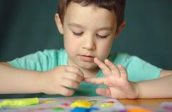 Παιχνίδι αγοριών με τη ζύμη παιχνιδιού χρώματος Στοκ Φωτογραφίες
