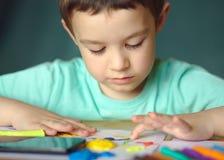 Παιχνίδι αγοριών με τη ζύμη παιχνιδιού χρώματος Στοκ Φωτογραφία