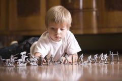 Παιχνίδι αγοριών με τους στρατιώτες παιχνιδιών στο πάτωμα Στοκ εικόνα με δικαίωμα ελεύθερης χρήσης