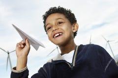 Παιχνίδι αγοριών με το αεροπλάνο εγγράφου στο αιολικό πάρκο Στοκ Φωτογραφίες