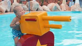 Παιχνίδι αγοριών με το πυροβόλο όπλο νερού φιλμ μικρού μήκους