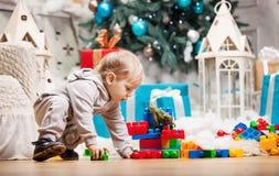 Παιχνίδι αγοριών μικρών παιδιών με τους φραγμούς στο χριστουγεννιάτικο δέντρο Στοκ Φωτογραφίες