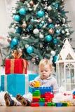 Παιχνίδι αγοριών μικρών παιδιών με τους φραγμούς στο χριστουγεννιάτικο δέντρο Στοκ Εικόνες