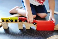 Παιχνίδι αγοριών μικρών παιδιών με το ξύλινο τραίνο παιχνιδιών στο σπίτι Στοκ Φωτογραφία