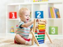 Παιχνίδι αγοριών παιδιών με τον άβακα Στοκ εικόνα με δικαίωμα ελεύθερης χρήσης