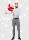 Παιχνίδι ατόμων χαμόγελου με το κόκκινο σημάδι πώλησης πέρα από το χιόνι Στοκ Φωτογραφίες