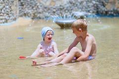 Παιχνίδι αδελφών και αδελφών υπαίθρια στην πισίνα Στοκ Φωτογραφία