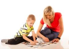Παιχνίδι γρίφων παιχνιδιού μητέρων με το γιο της Στοκ Φωτογραφίες