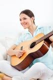 παιχνίδι εκμάθησης κιθάρων στη γυναίκα Στοκ Εικόνες