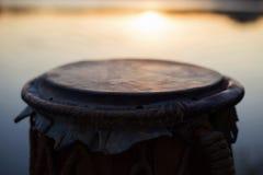 Παιχνίδι ενός μουσικού οργάνου jembe ή atabaque στον ουρανό υποβάθρου στο ηλιοβασίλεμα Στοκ Εικόνες