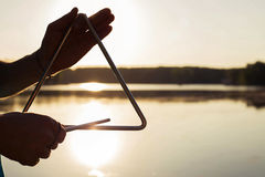 Παιχνίδι ενός μουσικού τριγώνου οργάνων στον ουρανό υποβάθρου στο ηλιοβασίλεμα Στοκ φωτογραφία με δικαίωμα ελεύθερης χρήσης
