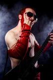 Παιχνίδι, κιθαρίστας με την ηλεκτρική κιθάρα μαύρη, φορώντας τον πόνο προσώπου Στοκ Φωτογραφία