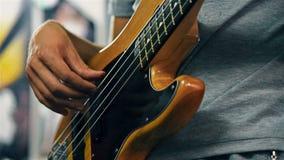 Παιχνίδι κιθαριστών στην ηλεκτρική βαθιά κιθάρα απόθεμα βίντεο