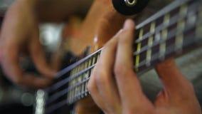 Παιχνίδι κιθαριστών χεριών στη βαθιά κιθάρα φιλμ μικρού μήκους