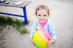 Παιχνίδι κοριτσάκι με μια χρωματισμένη σφαίρα στην παιδική χαρά Στοκ Φωτογραφία