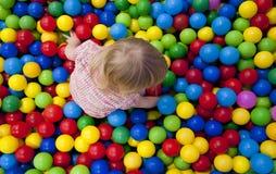Παιχνίδι κοριτσάκι στη ζωηρόχρωμη λίμνη σφαιρών παιδικών χαρών Επισκόπηση Closup Στοκ Φωτογραφία