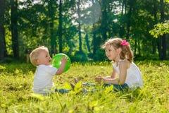 Παιχνίδι κοριτσιών και αγοριών με τη σφαίρα Στοκ Φωτογραφία