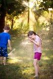 Παιχνίδι κοριτσιών και αγοριών στον ψεκαστήρα Στοκ φωτογραφία με δικαίωμα ελεύθερης χρήσης