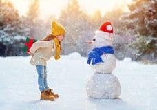 Παιχνίδι κοριτσιών με έναν χιονάνθρωπο στοκ φωτογραφία με δικαίωμα ελεύθερης χρήσης