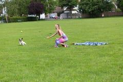 Παιχνίδι κοριτσιών με ένα εύθυμο σκυλί Στοκ Εικόνα